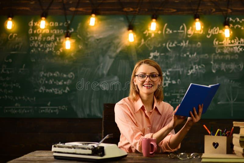 O secretário trabalha na secretaria da escola o secretário da mulher lê o caderno busca para o trabalho do secretário imagem de stock