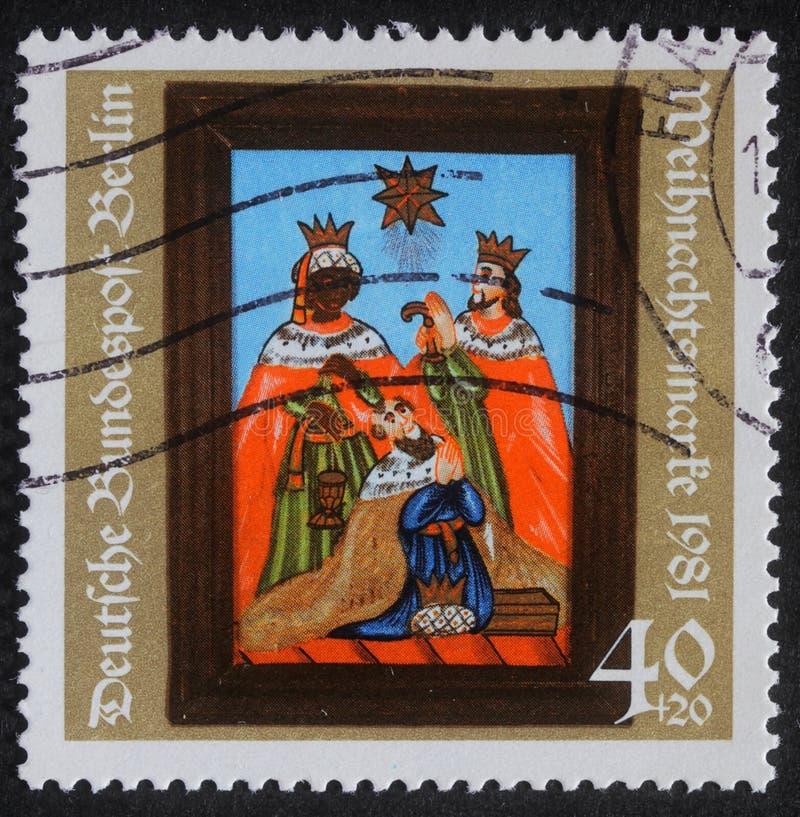 O selo do Natal impresso em Alemanha mostra o nascimento de Jesus Christ, adoração dos três Reis Magos imagens de stock