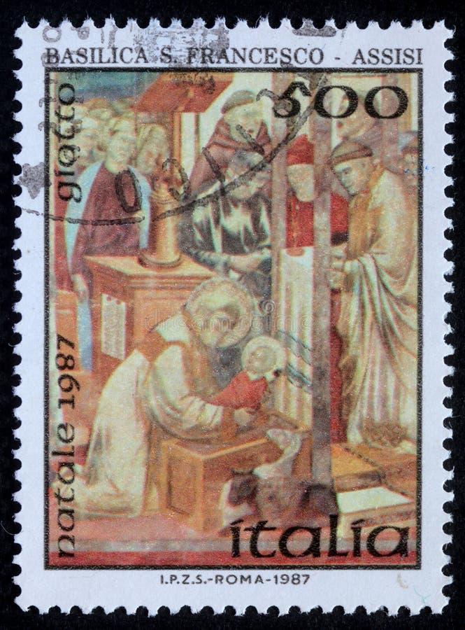 O selo do Natal impresso em mostras de Itália tira pelo artista Giotto - nascimento de Jesus Christ fotografia de stock royalty free