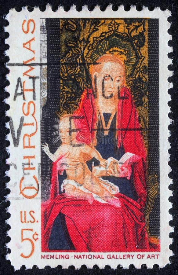 O selo do Natal impresso em mostras dos EUA tira pelo artista Memling - Madonna e criança imagem de stock