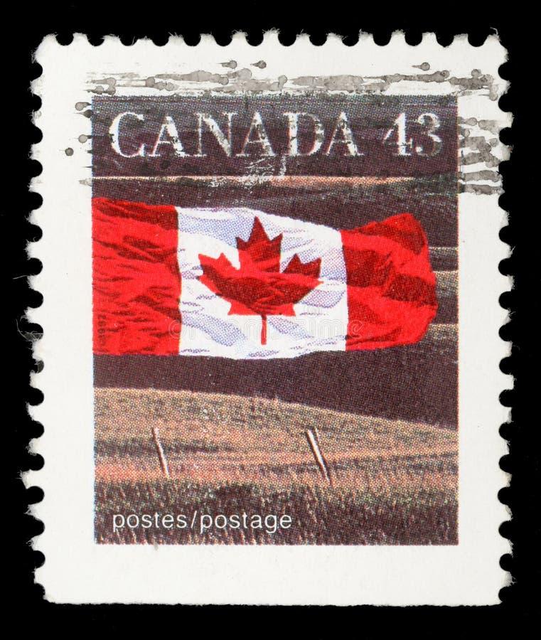 O selo impresso em Canadá mostra a bandeira e a pradaria canadenses fotografia de stock