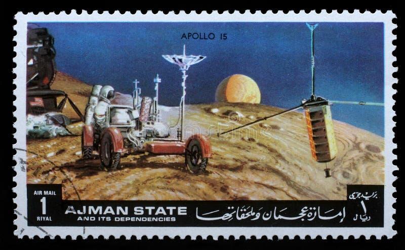 O selo impresso por Ajman mostra Apollo 15 - transmissão de tevê imagem de stock royalty free
