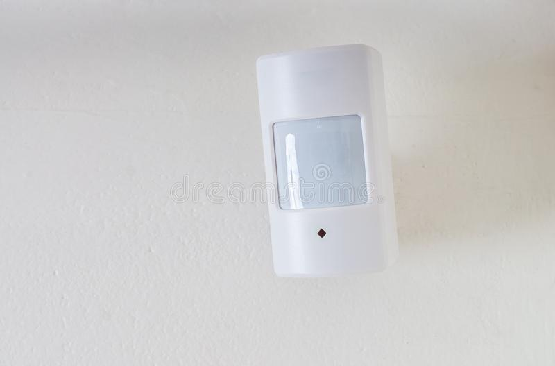 O sensor ou o detector de movimento para o sistema de segurança montaram na parede foto de stock royalty free