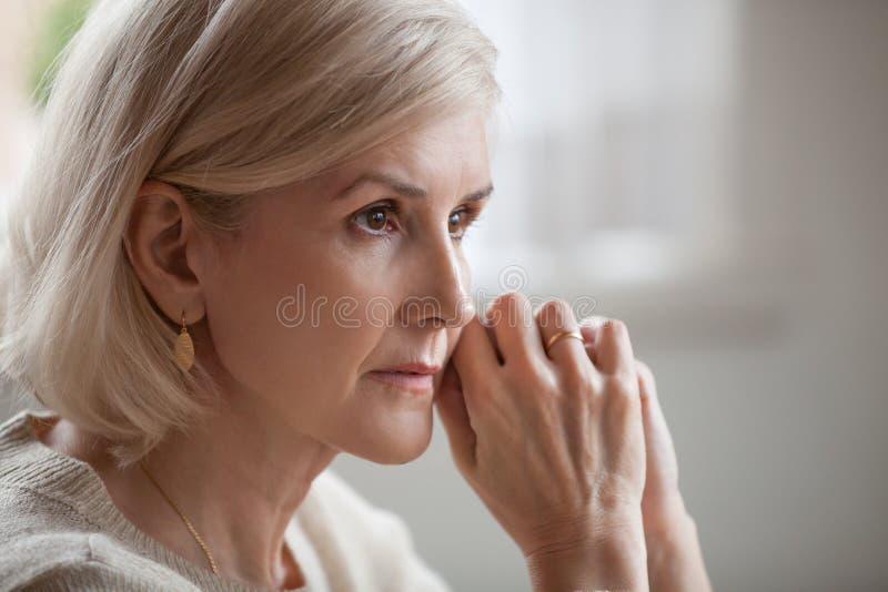 O sentimento superior maduro ansioso sério pensativo da mulher preocupou a imagens de stock