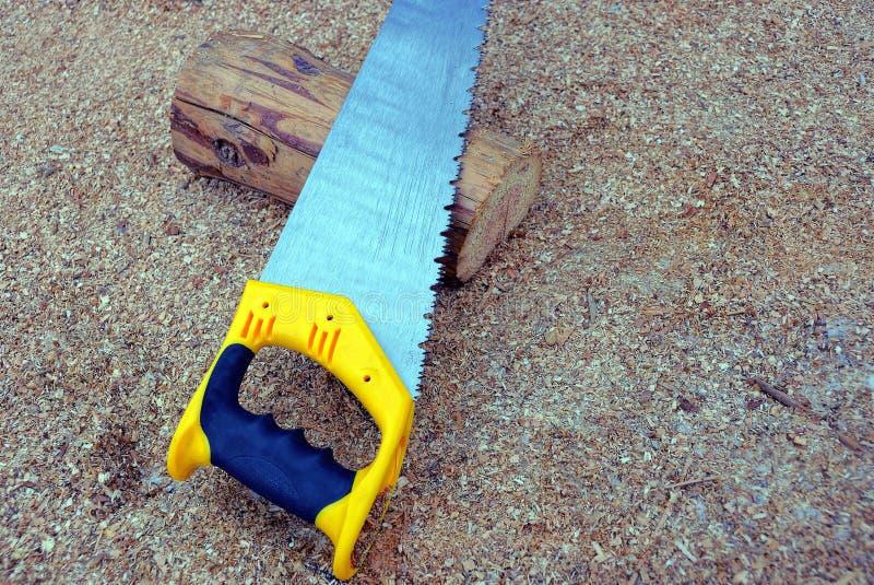 O serrote do metal encontra-se em um log marrom de madeira aparado fotografia de stock