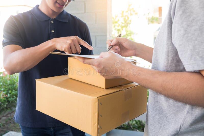 O serviço da entrega a domicílio entrega o pacote em casa e a mulher que recebe assinando para a ordem de compra em linha foto de stock