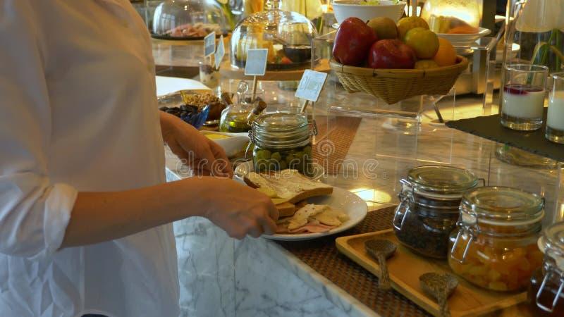 O serviço do auto tomou o alimento da linha do bufete a mulher está preparando um sanduíche para o café da manhã foto de stock