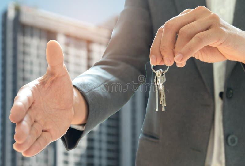 O shakehand das vendas home e a outra mão guardam a chave da casa Fundo mim fotos de stock royalty free