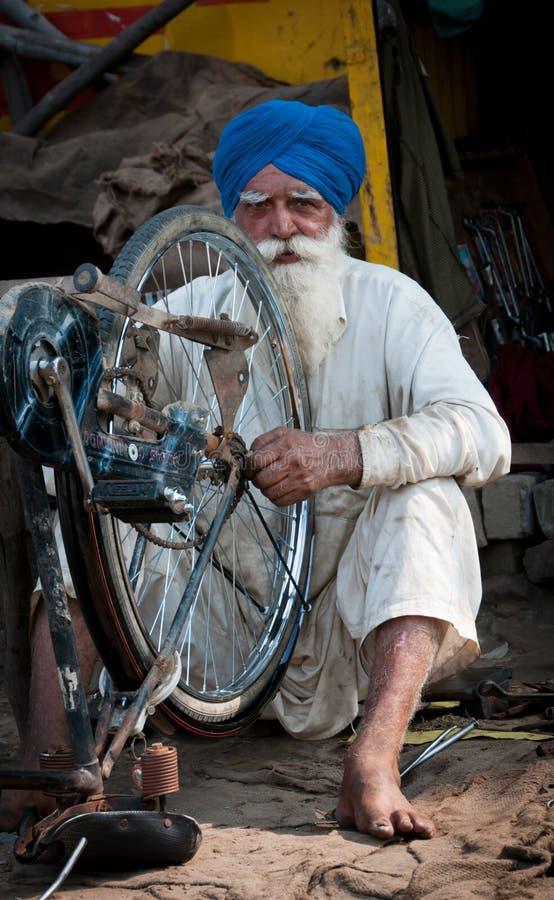 O sikh do homem idoso está reparando o ciclo fotografia de stock