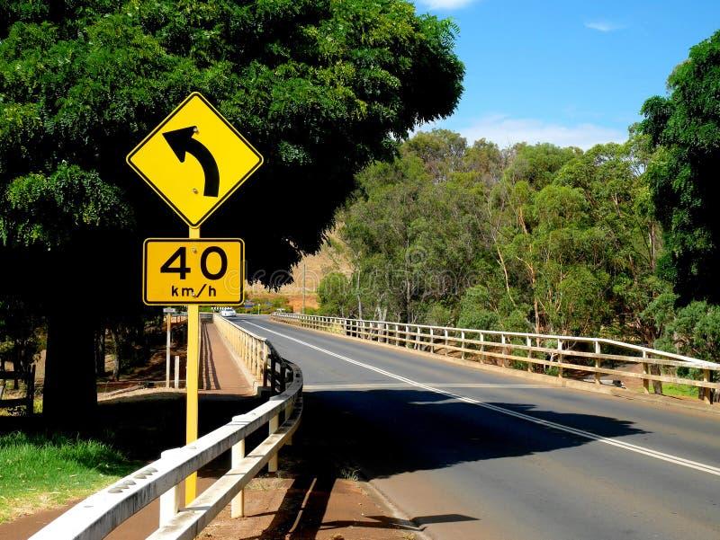 O sinal da curva adiante e o limite de velocidade esquerdos assinam foto de stock royalty free