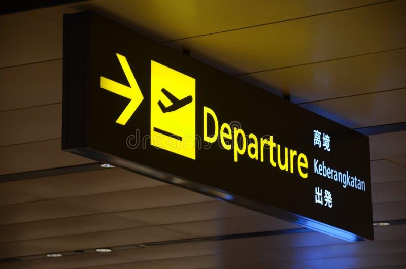 O sinal da partida pendura sobre viajantes ocupados no salão da partida do terminal de aeroporto 1 de Changi fotografia de stock royalty free