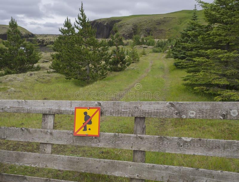 O sinal de aviso não faz tombadilho aqui para humanos, povos do turista, na cerca de madeira, paisagem bonita de Islândia no fund fotografia de stock