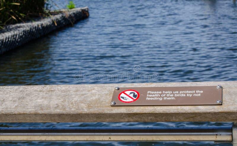 O sinal de aviso para o ` ajuda-nos por favor a proteger a saúde dos pássaros não alimentando lhes o ` perto da lagoa no pantanal fotografia de stock royalty free