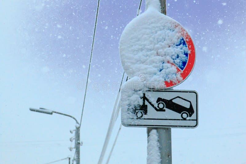 O sinal de estrada uma parada é proibido e o caminhão de reboque é levado pela neve em um fundo do céu imagem de stock