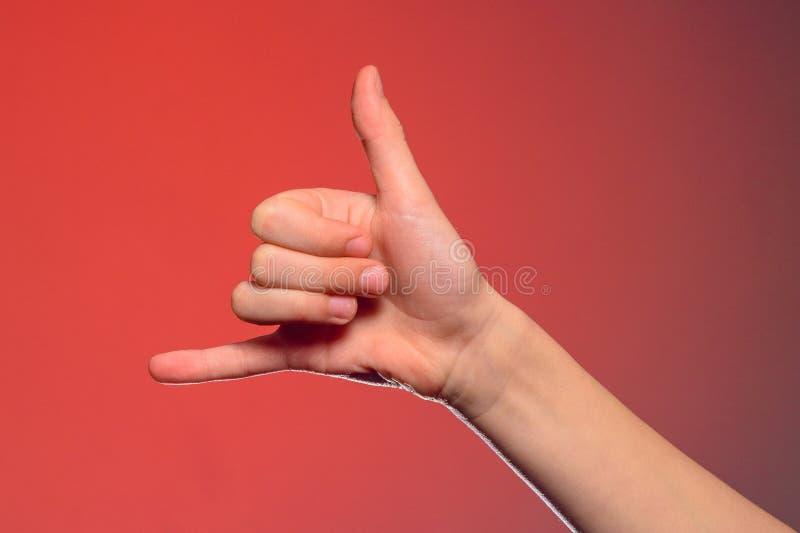 O sinal de mostras de um telefonema isolado one-handed em um fundo vermelho foto de stock