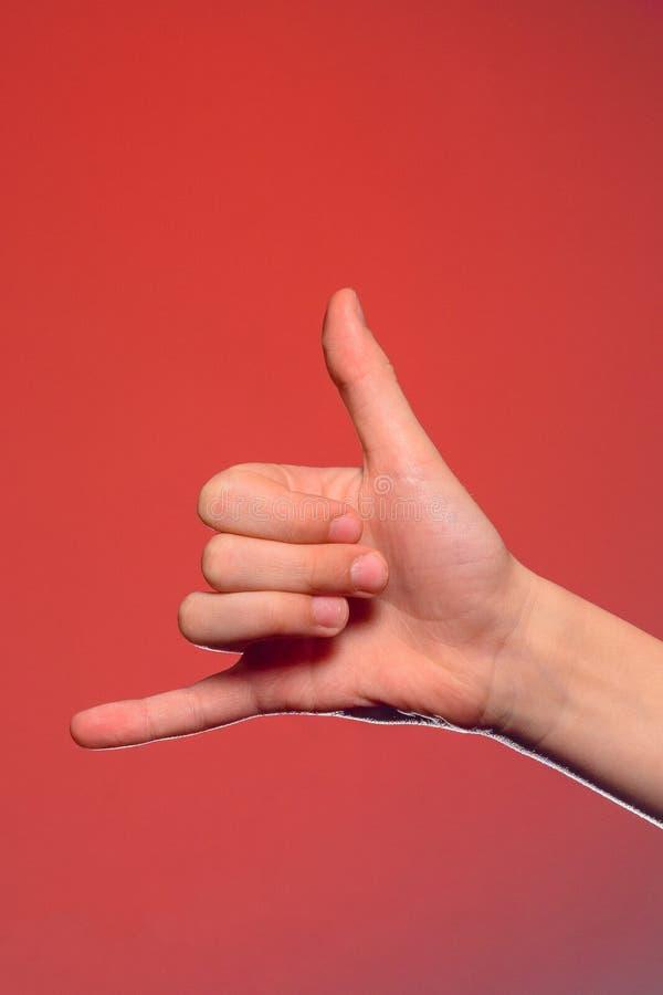 O sinal de mostras de um telefonema isolado one-handed em um fundo vermelho fotografia de stock