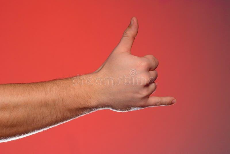 O sinal de mostras de um telefonema isolado one-handed em um fundo vermelho fotos de stock royalty free