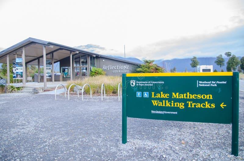 O sinal de passeio das trilhas de Matheson do lago na entrada, conduz às vistas das montanhas refletidas nas águas imóveis do lag fotografia de stock