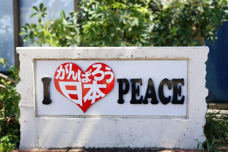 O sinal de pedra onde é inscreido em uma forma do coração mim ama a paz deixou-nos fazer nosso melhor Japão na alameda da loja do fotos de stock