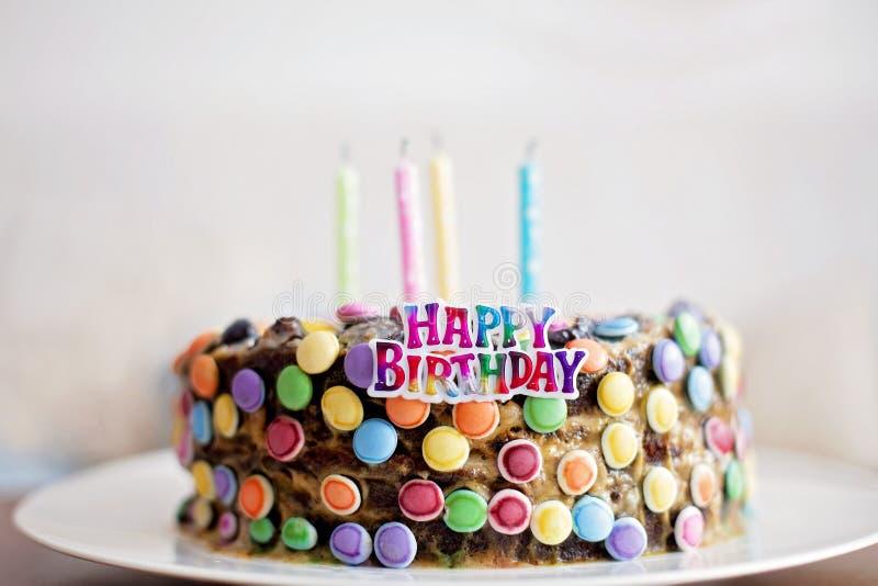 O sinal e as velas do feliz aniversario em doces da criança endurecem imagem de stock