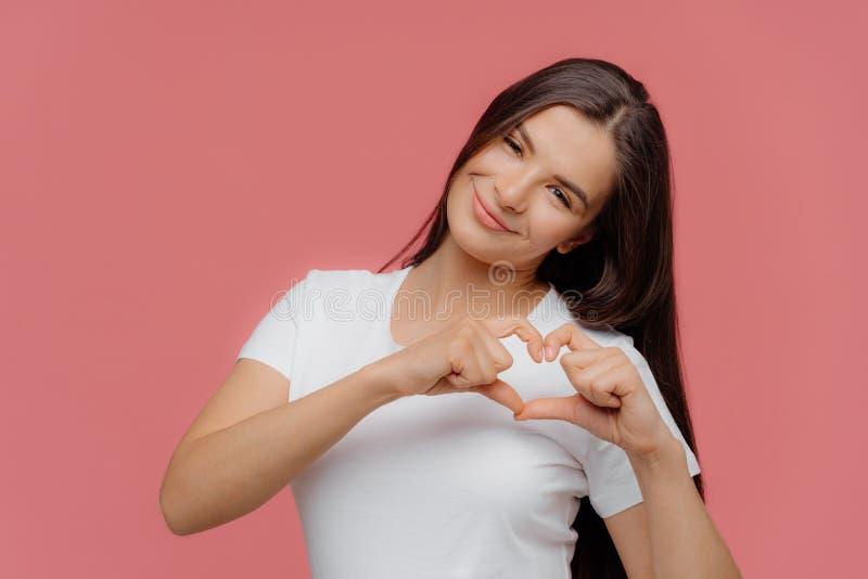 O sinal fêmea moreno satisfeito de sorriso do coração das formas do modelo, expressa o amor ao noivo, vestido na camisa branca oc foto de stock royalty free