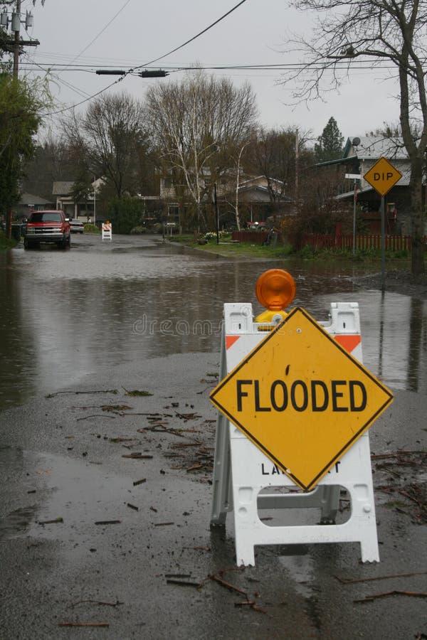 O sinal inundado senta-se em uma rua inundada imagem de stock