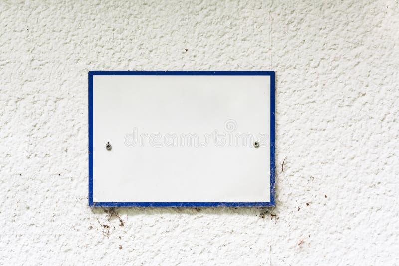 O sinal ou o painel montaram com beira azul sem inscrição em uma parede ilustração stock