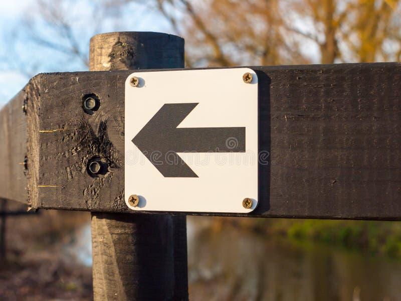 O sinal preto e branco da maneira do sentido saiu do outsid de madeira preto do cargo imagens de stock
