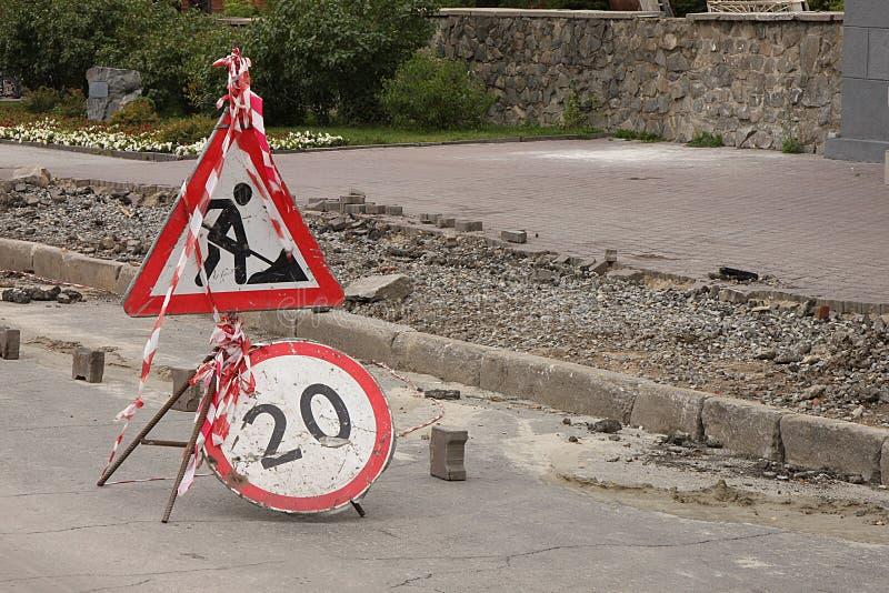 O sinal restritivo nos reparos do passeio e o limite de velocidade do sinal dentro de 20 km/h são oposto ao lugar dos reparos fotos de stock royalty free
