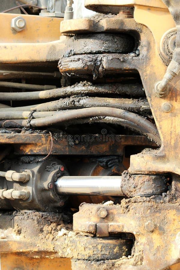 O sistema e as mangueiras hidráulicos do pistão do trabalho sujo para o carregador, cromo chapearam o eixo do cilindro da máquina fotografia de stock royalty free