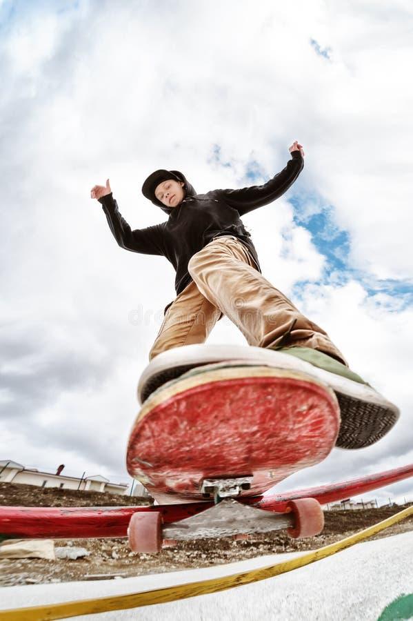 O skater adolescente em uma camiseta e em calças de brim do hoodie desliza sobre uns trilhos em um skate em um parque do patim fotos de stock royalty free