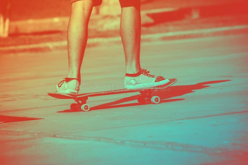 O skater masculino em um skate está montando no por do sol fotografia de stock