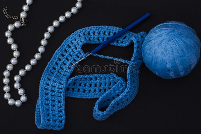 O Skein da linha azul com faz crochê e fazendo malha no fundo preto com os grânulos da pérola para mulheres imagem de stock royalty free
