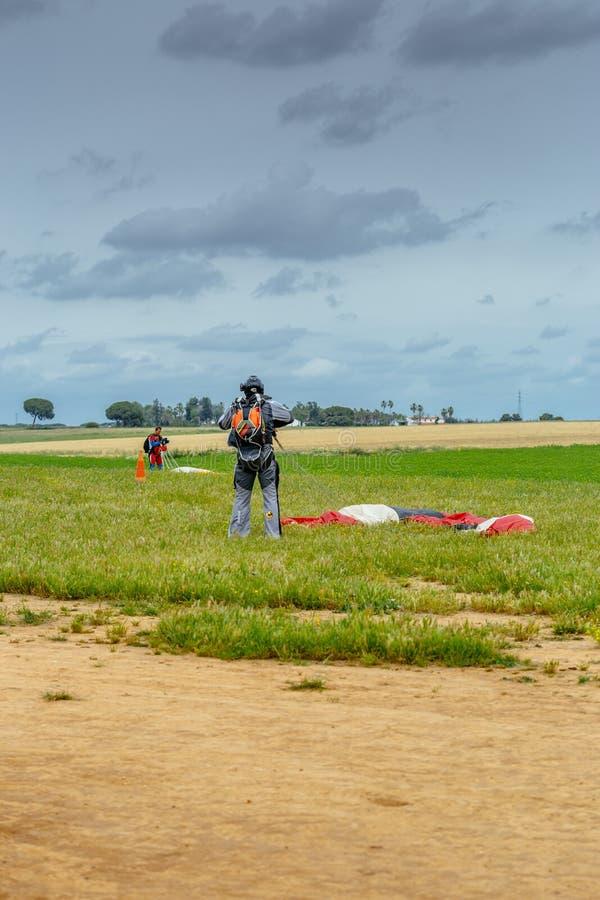 O Skydiver desata seu paraquedas após a aterrissagem foto de stock