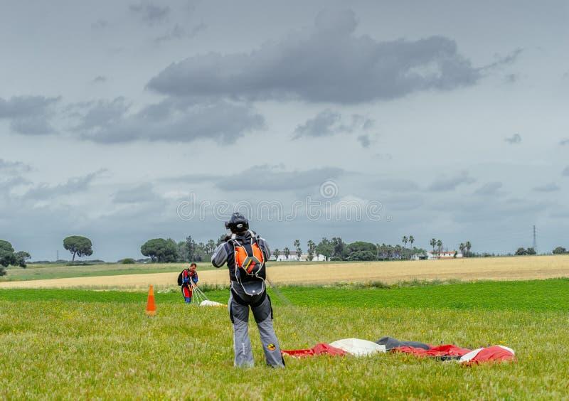 O Skydiver desata seu paraquedas após a aterrissagem fotografia de stock