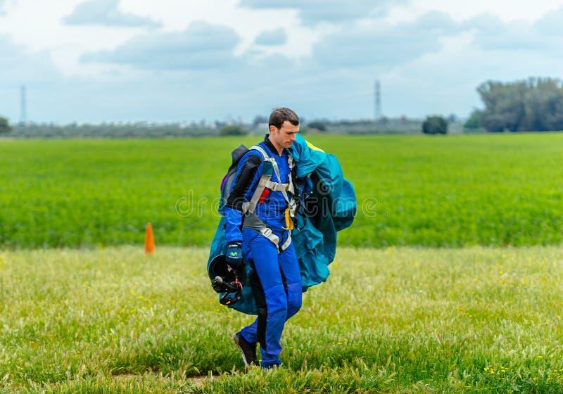 O Skydiver leva um paraquedas após a aterrissagem foto de stock royalty free