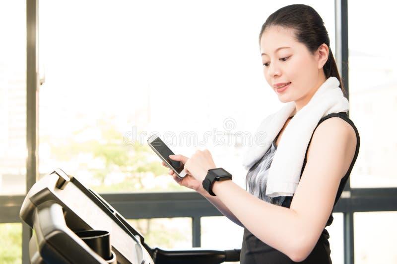 O smartwatch running do uso da escada rolante da mulher asiática bonita conecta s imagens de stock royalty free