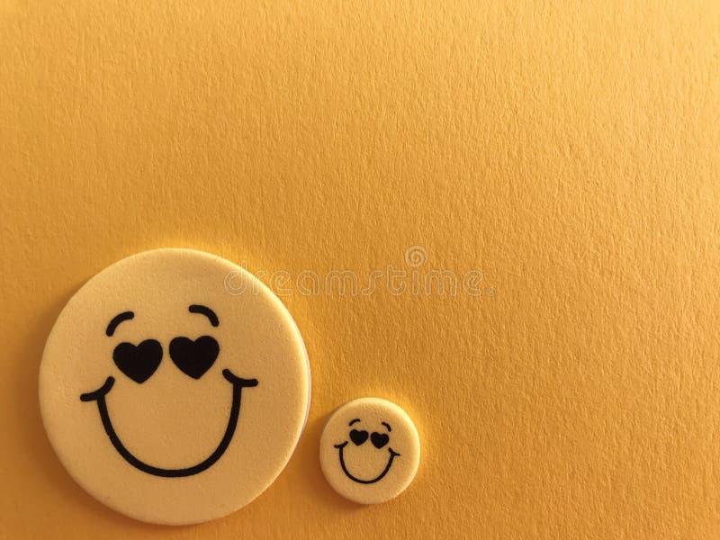 O smiley amarelo enfrenta no amarelo fotos de stock