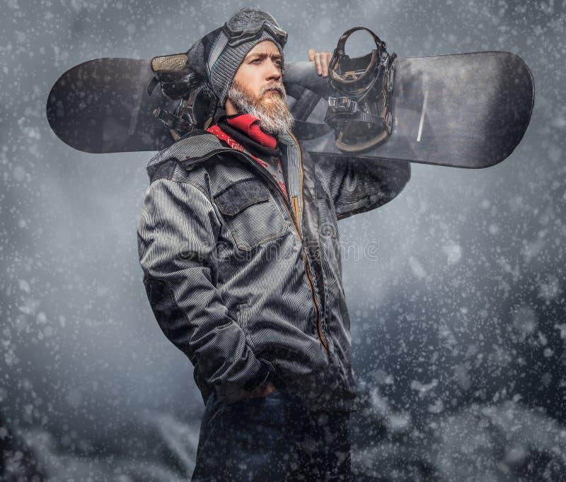 O snowboarder brutal do ruivo com uma barba completa em um chapéu e em uns vidros protetores do inverno vestiu-se em um revestime fotos de stock