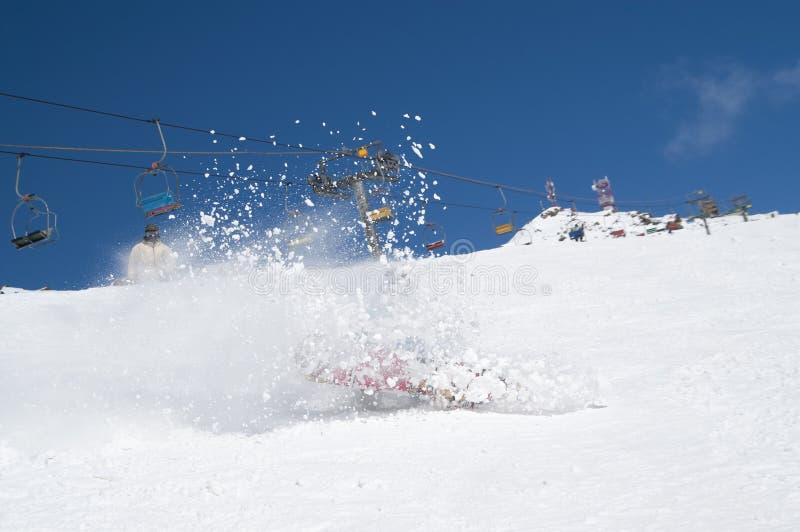 O Snowboarder cai para baixo com neve espirra na inclinação nevado do esqui foto de stock