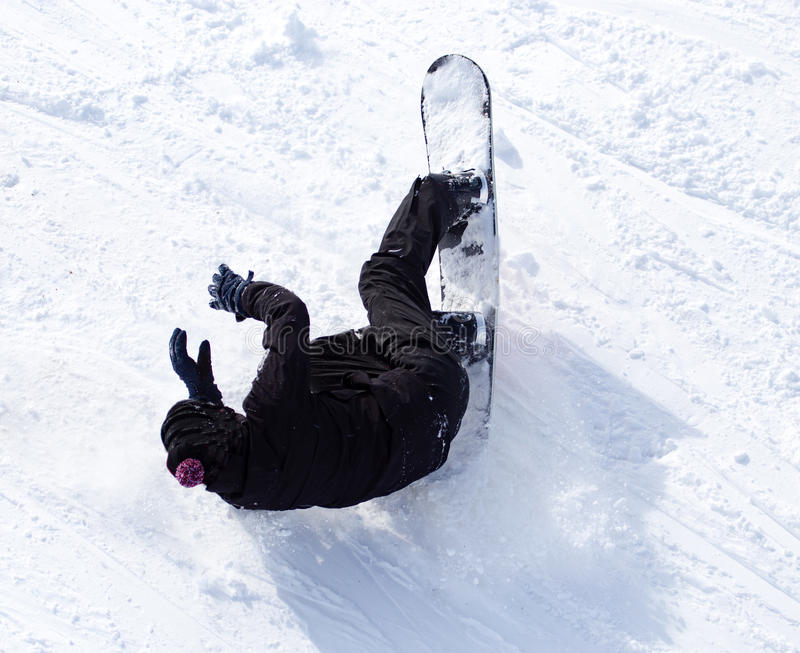 O Snowboarder caiu na neve na velocidade foto de stock