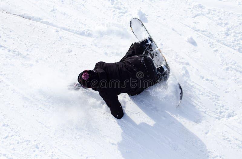 O Snowboarder caiu na neve na velocidade imagem de stock royalty free