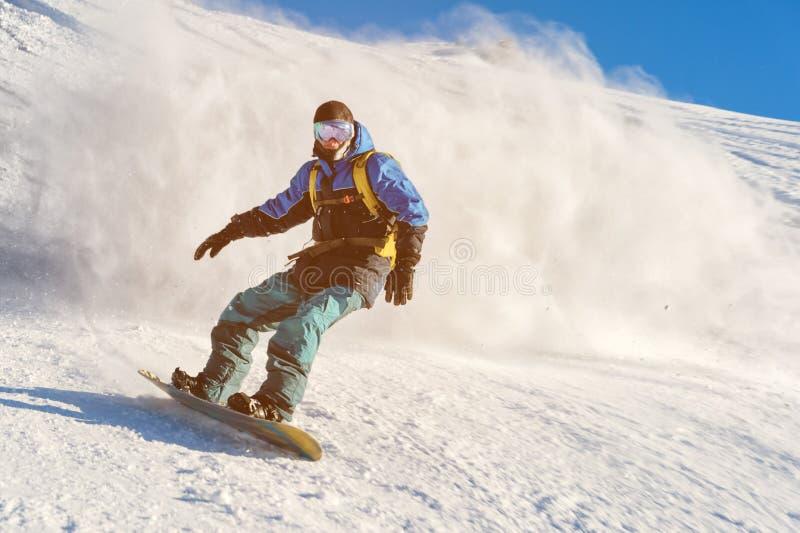 O snowboarder de Freeride rola em uma inclinação coberto de neve que sae atrás de um pó da neve contra o céu azul fotografia de stock