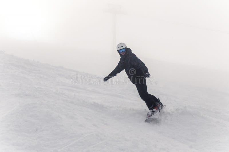 O Snowboarder desce de uma montanha alta em uma inclinação no dia frio do inverno imagens de stock royalty free