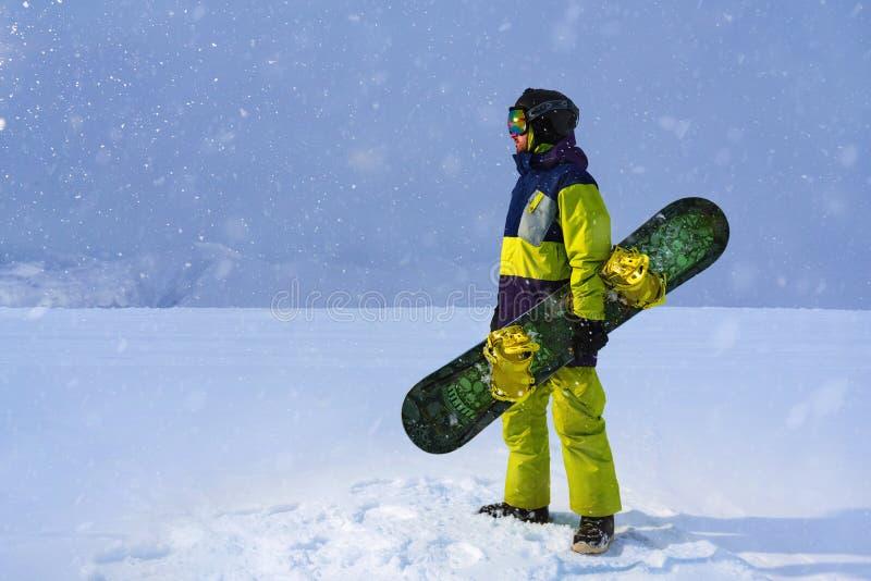 O Snowboarder leva uma placa nas mãos Queda de neve da noite nas montanhas fotos de stock