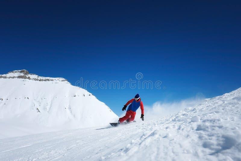 O snowboarder masculino à moda do atleta monta em um quadro-negro no sn fotos de stock royalty free