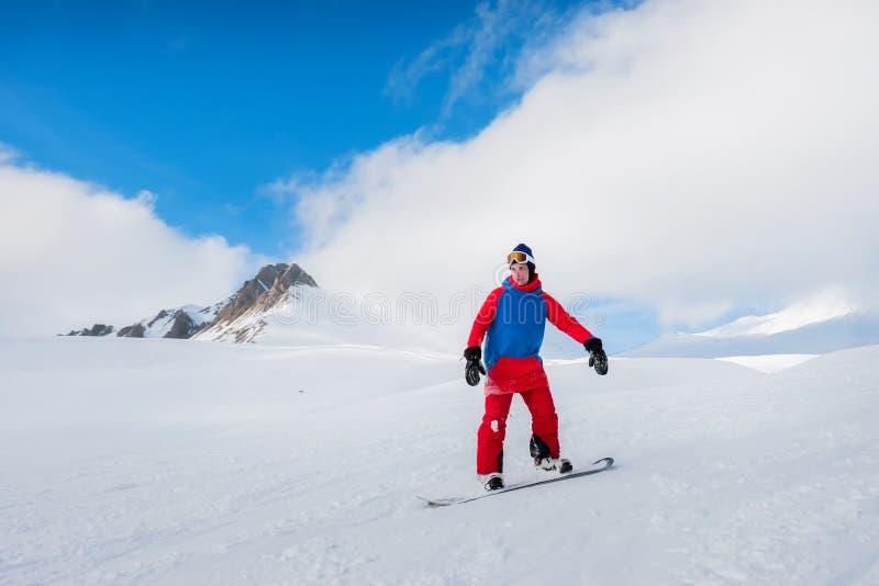 O snowboarder masculino à moda do atleta monta em um quadro-negro no sn imagem de stock