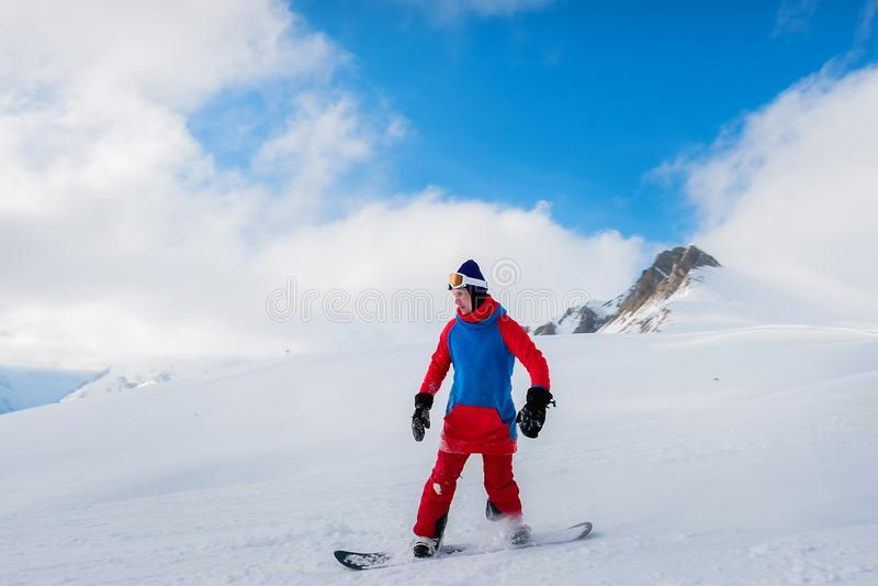 O snowboarder masculino à moda do atleta monta em um quadro-negro no sn foto de stock royalty free