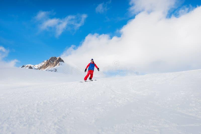 O snowboarder masculino à moda do atleta monta em um quadro-negro no sn foto de stock