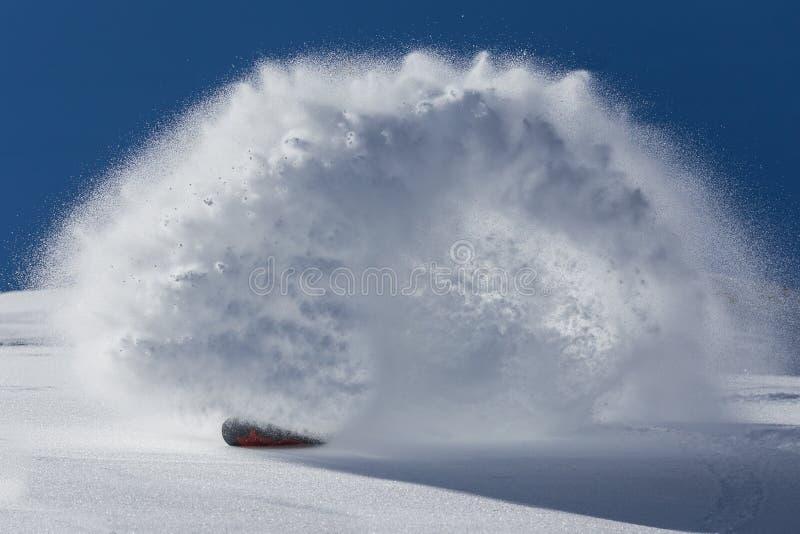 O snowboarder masculino curvou-se e os freios que pulverizam a neve profunda fraca na inclinação do freeride imagem de stock royalty free